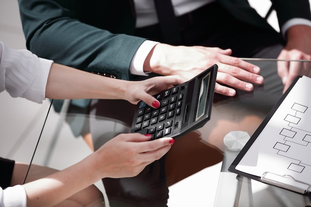 Крупным планом. деловая женщина, работающая с калькулятором