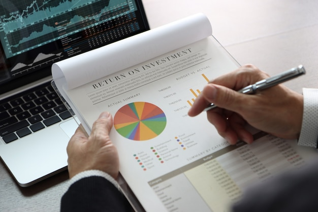 Closeup on businessman or analyst hands holding financial statements reviewing on return on investment, roi, investment risk analysis in front of laptop computer with graphs and related information