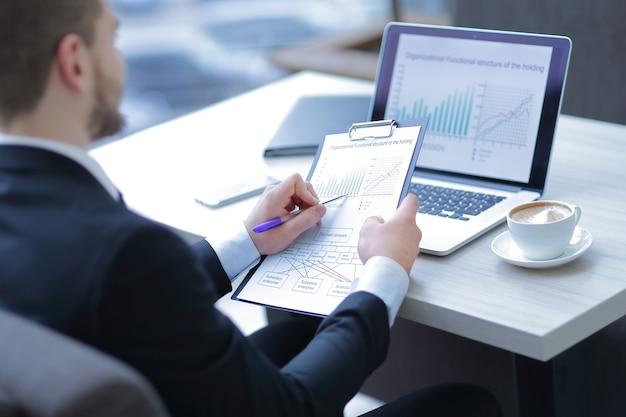 사무실에서 책상에 앉아 금융 문서를 확인하는 closeup.businessman.