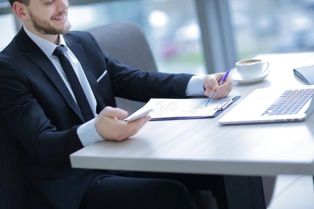 Крупным планом. бизнесмен, проверяющий финансовый отчет, сидя за столом в офисе
