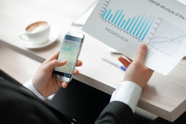 Крупным планом. бизнесмен проверяет финансовые данные с помощью смартфона