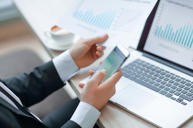 クローズアップ。ビジネスマンはスマートフォンを使用して財務データをチェック