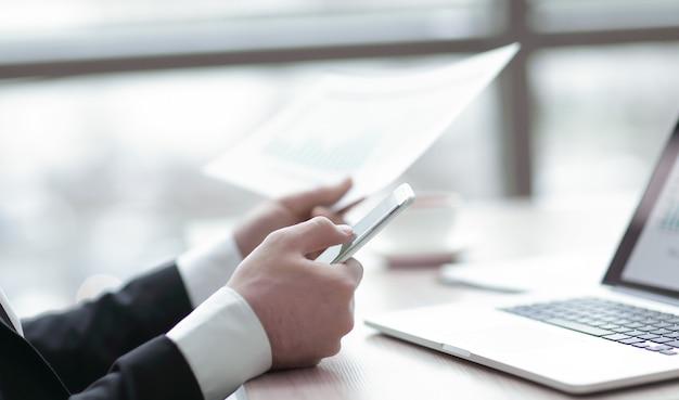 Крупный план. бизнесмен проверяет финансовые данные с помощью смартфона