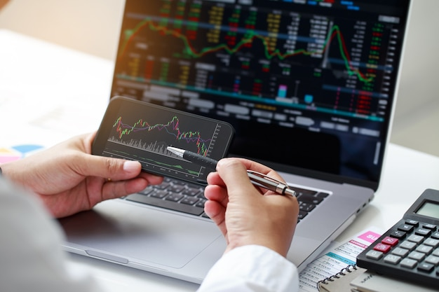 Крупным планом бизнесмен рука держит телефон и анализ график финансового рынка торговля на фондовом рынке