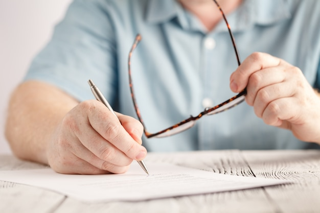Closeup of businessman hands writing something on piece of paper and holding pair of glasses