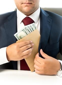 Бизнесмен крупным планом, пряча конверт с деньгами в кармане на куртке