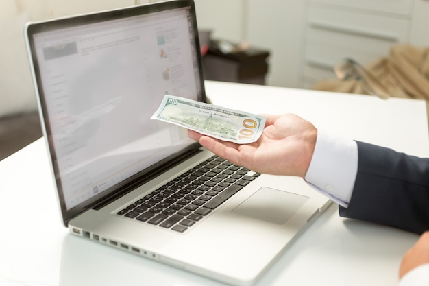 Closeup businessman holding banknote on hand and giving it to computer