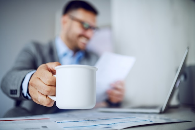Closeup of businessman holding coffee.