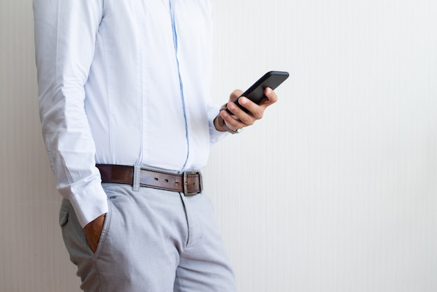 Closeup of businessman holding and using smartphone