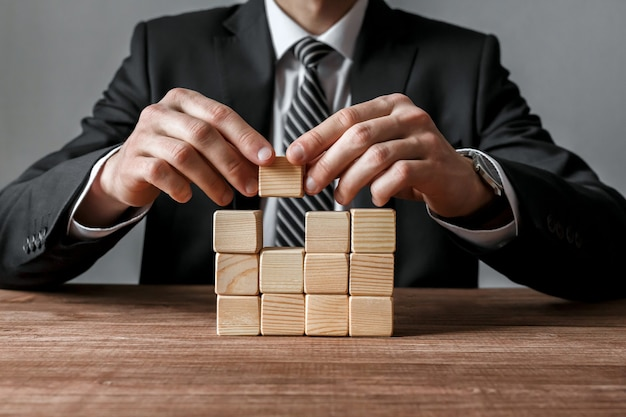 Closeup of businessman making a structure with wooden cubes. success and business strategy concept.