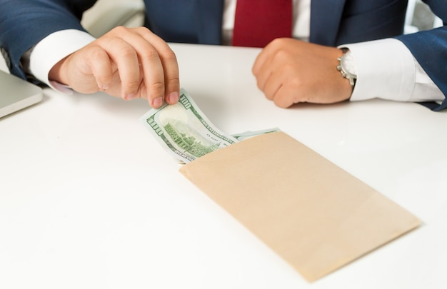 Closeup businessman pulling banknote out of envelope lying on table