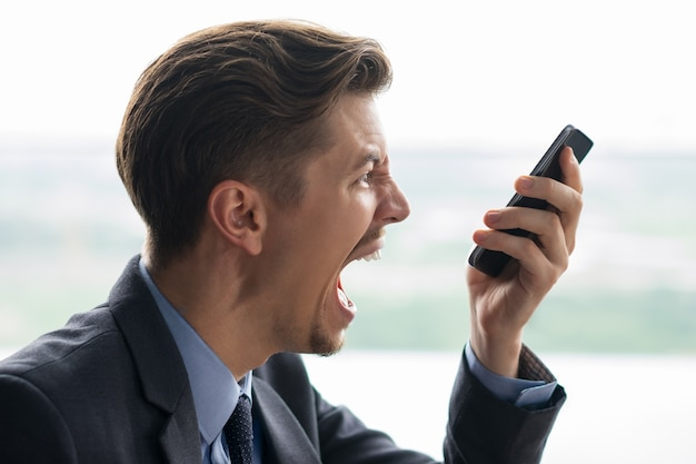 Closeup of businessman shouting at smartphone