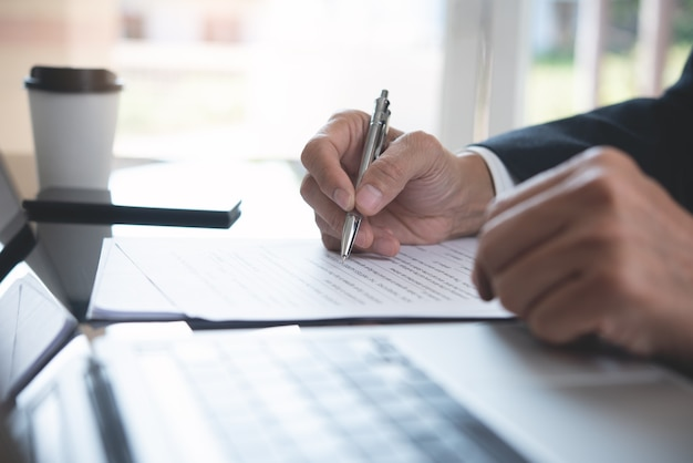 Closeup of businessman signing business contract at office