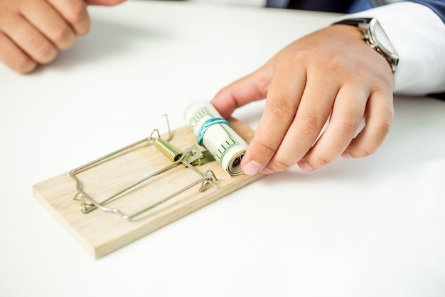 Closeup businessman taking money out of mousetrap