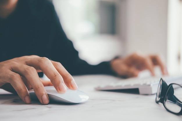 コンピューターのキーボードでコンピューターのマウスを使用してクローズアップ実業家