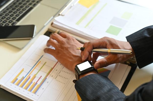 Closeup businessman using mockup smart watch on office desk.