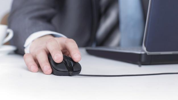 Крупным планом. бизнесмен, работающий на ноутбуке, сидя за своим столом. изолированные на белом фоне