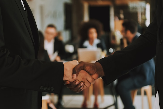 Closeup of businessmen is shaking hands each other.