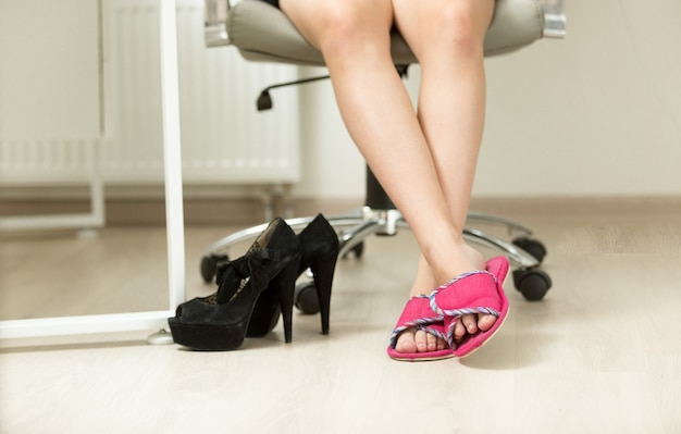 Closeup businesswoman feet in slippers under office table