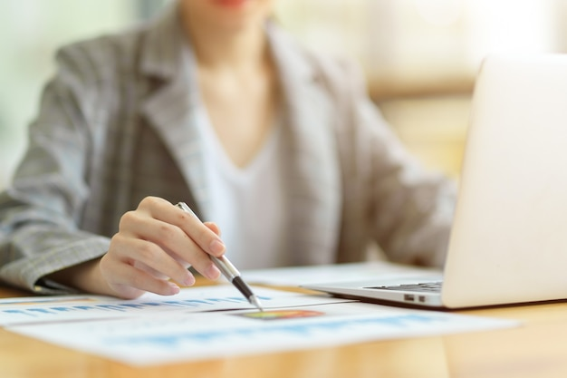 Closeup of businesswoman or female accountant sitting and working on laptop at desk. looking on business data report, pointing pen on paper