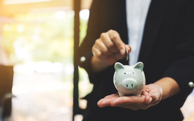 Closeup  of a businesswoman holding and putting coin into piggy bank for saving money and financial concept