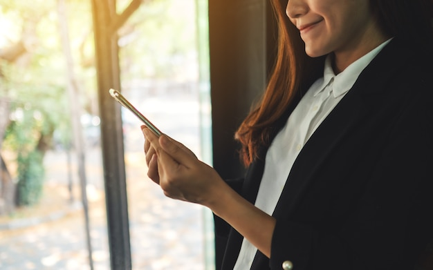 Closeup  of a businesswoman holding and using mobile phone indoors