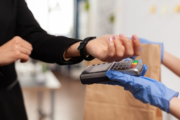 Closeup of businesswoman paying food order having contactless payment with smart watch using pos terminal service