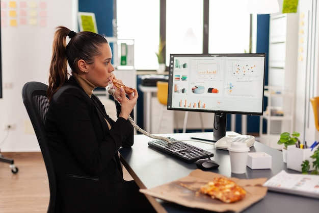 Closeup of businesswoman sitting at desk in front of computer eating pizza slice while talking at landline with remote company manager. lunch meal break package delivered at startup office.