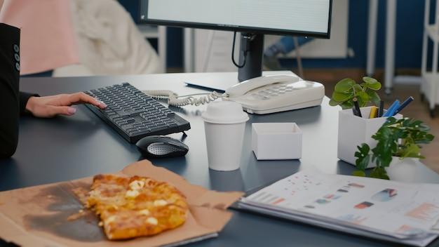 Primo piano di una donna d'affari seduta alla scrivania davanti al computer che mangia una fetta di pizza mentre parla al telefono fisso con il manager dell'azienda remota
