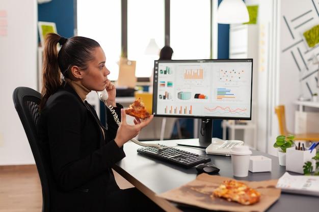 Primo piano di una donna d'affari seduta alla scrivania davanti al computer che mangia una fetta di pizza