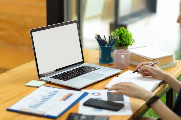 Крупным планом рабочее пространство бизнес-леди с макетом пустого экрана ноутбука, отчет о продажах на столе, женщина делает заметки