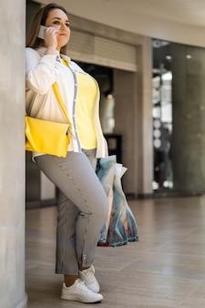 ショッピングモールで購入とバッグを持って笑顔のスマートフォンを話しているクローズアップバイヤー女性