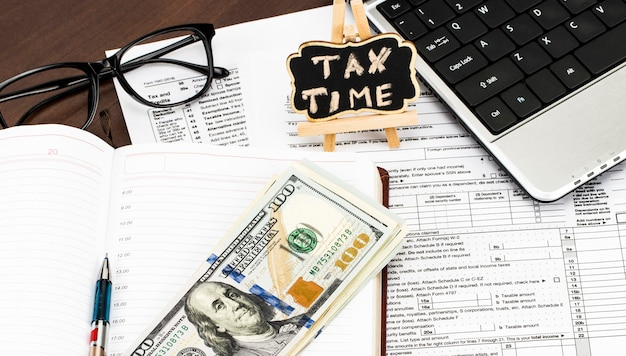 Closeup of calculator,  tax forms with the glasses, money and the pen and tax time written on chalkboard.