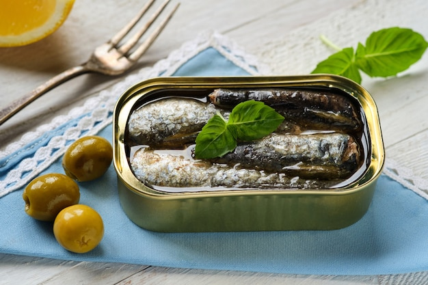 Closeup of can of sardines in oil, with a basil leaf and olives on blue napkin