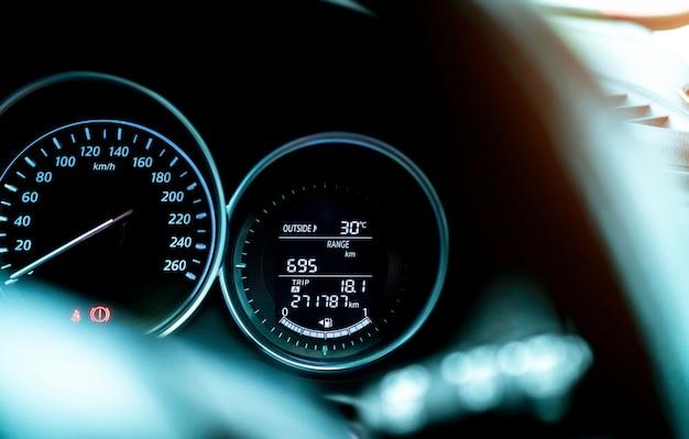Панель приборной панели датчика топлива автомобиля крупного плана. индикатор бензинового индикатора и спидометр. датчик уровня топлива показывает полный бензобак. на приборной панели отображается температура снаружи автомобиля, диапазон срабатывания и значок топливного бака.