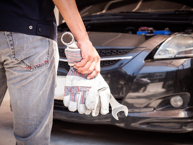 Closeup behind of car mechanic get ready to work. auto mechanic holding gloves and large wrench in hand.