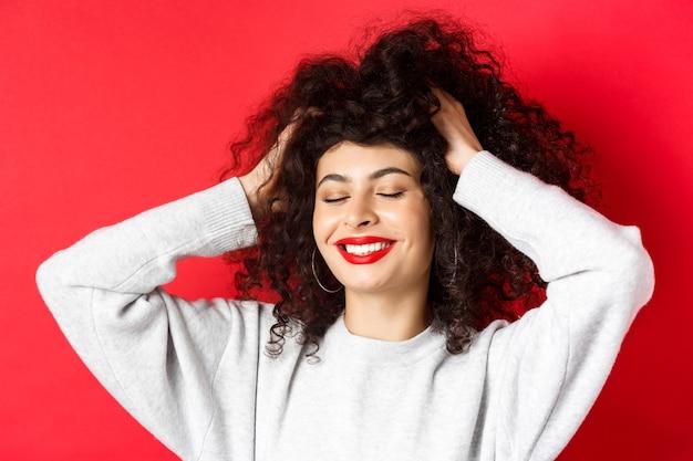 Primo piano di donna spensierata che tocca i capelli ricci morbidi e sorride compiaciuta in piedi su sfondo rosso ha...