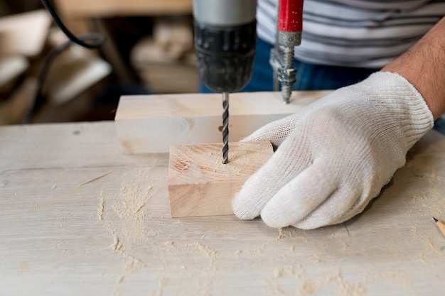 Closeup of carpenter using electric drill in workshop and routing out holes