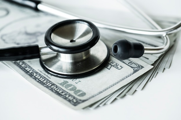 Closeup of cash and a stethoscope healthcare and expenses concept