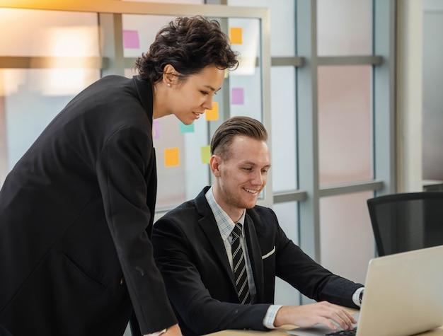Кавказский бизнесмен крупного плана счастлив посоветовать коммерсантку, используя компьтер-книжку. позитивный настрой, работая вместе с партнерством. мужчина и женщина коллега отношения в офисе.