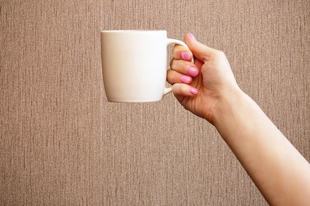 Closeup caucasian female hand holding white cup of morning tea or coffee on brown background with