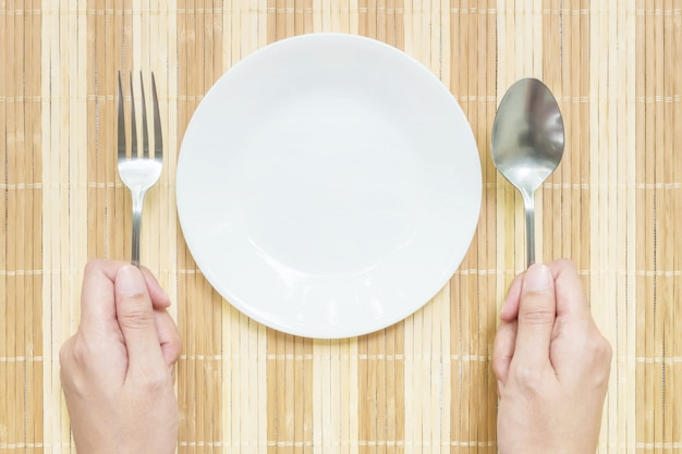 Closeup ceramic dish with stainless fork and spoon in woman hand on mat background