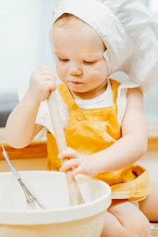 Closeup of a charming hardworking little girl in a chef hat stirs a pancake dough with a whisk