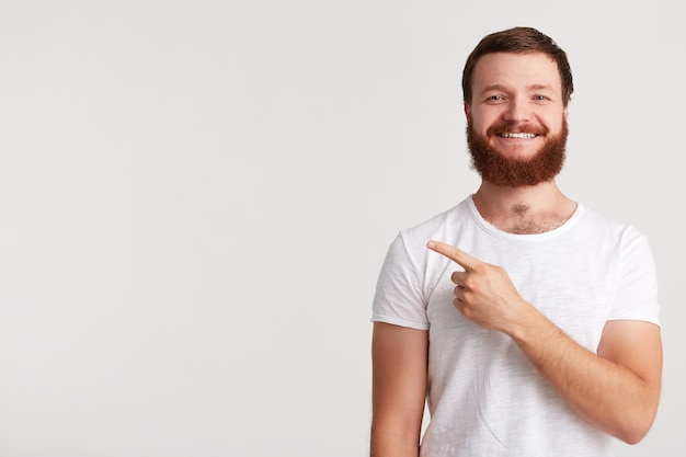 Closeup of cheeful confident young man hipster with beard wears t shirt feels happy and points to the side with finger isolated over white wall