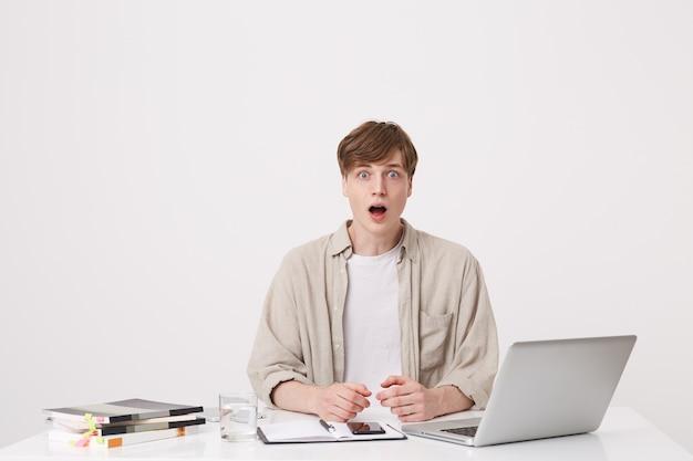 Primo piano di allegro giovane studente maschio con le parentesi graffe indossa lo studio camicia beige utilizzando computer portatile e notebook seduto al tavolo isolato sopra il muro bianco