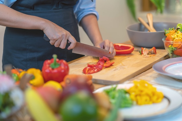 Closeup chef hand cutting the bell pepper on the chopping board in modern kitchen