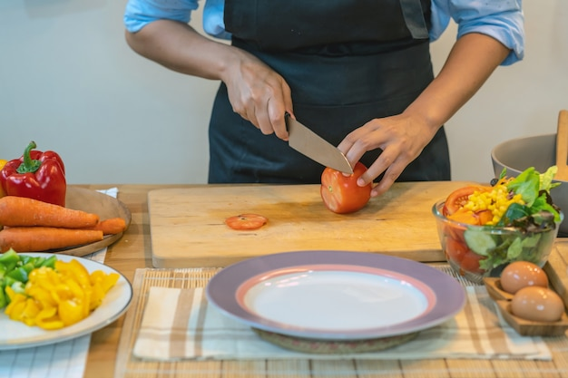 Closeup chef hand cutting the tomato on the chopping board in modern kitchen