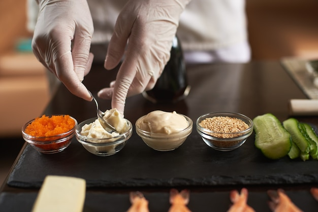 Closeup of chef hands preparing components for cooking rolling sushi at restaurant.