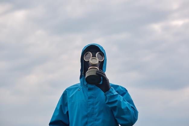 屋外でポーズをとるクローズアップ化学科学者または生態学者、青い制服と防毒マスクを身に着け、科学者は周囲を探検し、私たちの環境を保護することを求めます。生態学の概念。