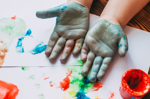 Closeup of child hands in blue paint the child is drawing on white sheets with finger paints